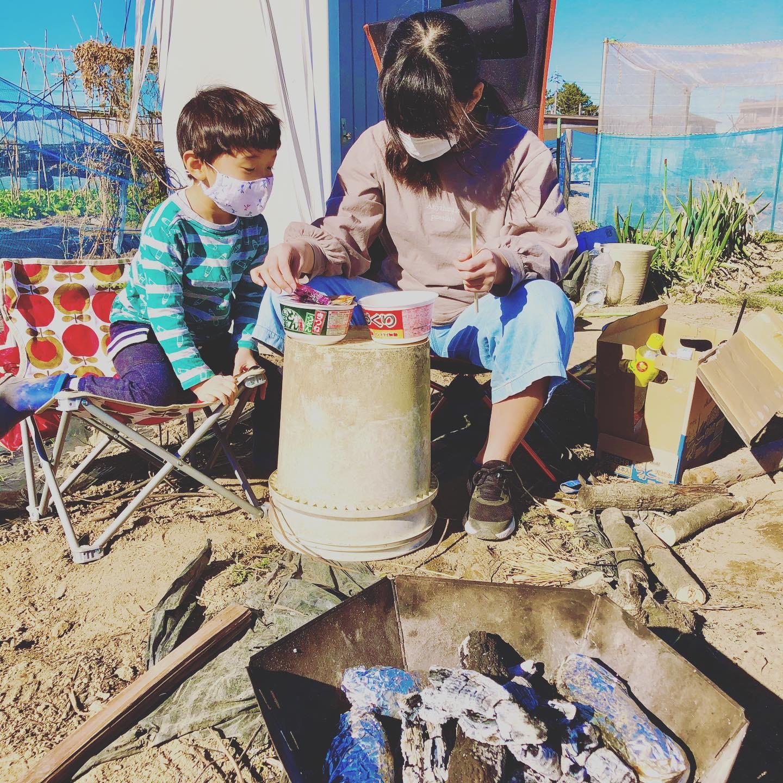 出かけたいという子どもの気を紛らわすために畑で焚き火。新年のお飾りをお焚き上げして神様をお見送り。今日のお昼ご飯はその火でお湯を沸かしてカップラーメンと焼き芋。今年一年健康に過ごせますように。#家庭菜園 #菜園 #貸し農園 #サイエナー #わたしの野菜生活 #焚き火 #焼き芋 - 畑での一コマ